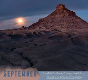 Morning glow and moonset over the Cretaceous-age Mancos Formation of Factory Butte, Wayne County. Photographed by Gregg Beukelman.